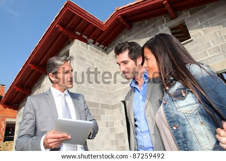 Real-estate agent showing house under construction to couple