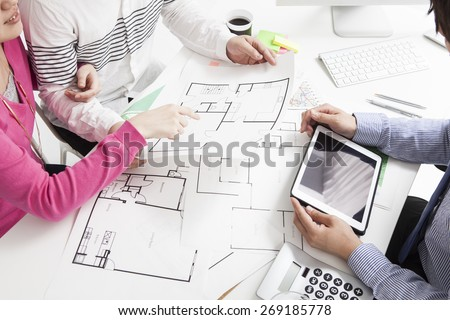 Real-estate agent shows a build project on a digital tablet to a young couple
