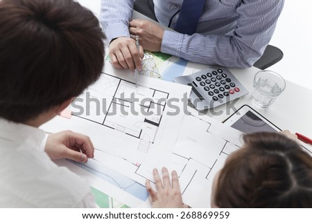Real-estate agent shows a build project to a young couple