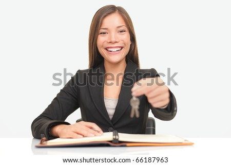 Real estate agent sitting at desk giving house keys smiling to new home owners.