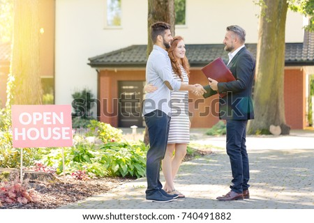 Real estate agent welcoming young visitors coming to open house