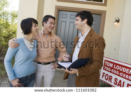 Real estate agent with asian couple buying new house