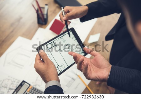 Real estate agent with client or architect team discussing a housing model and its blueprints digitally using a tablet computer #722932630