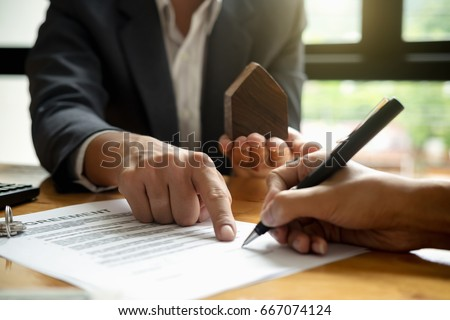 Real estate agent with house model hand putting signing contract,have a contract in place to protect it,signing of modest agreements form in office.Concept real estate,moving home or renting property