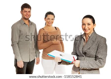 Real estate agent woman with contract and keys in front of image while a pregnant couple smiling in background