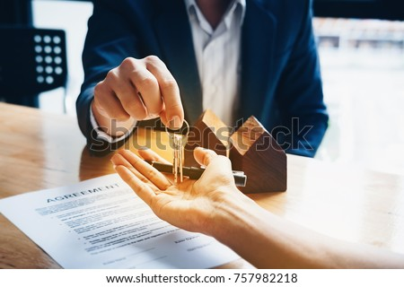 Real estate agents agree to buy a home and give keys to clients at their agency's offices. Concept agreement #757982218