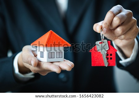 Real estate agents hold the keys to the red house and the orange house to put on their hands. Ideas for real estate, moving homes, or renting real estate Trading houses have space for entering text.