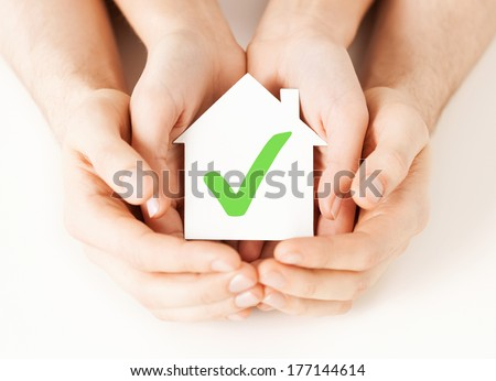 real estate and family home concept - male and female hands holding paper house with green check mark
