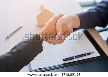 Real estate broker agent Shake hands after customer signing contract document for ownership realty purchase in the office, Business concept and  signing contract