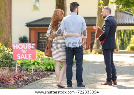 "Real estate broker and clients standing next to plate with inscription ""house for sale"" #722335354"