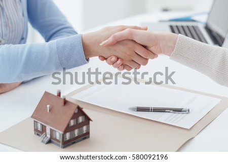 Real estate broker and customer shaking hands after signing a contract: real estate, home loan and insurance concept
