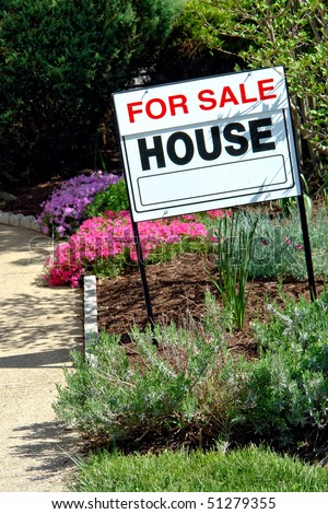 Real estate broker for sale rider insert on a Realtor sign on the flower garden in front of a house for sale