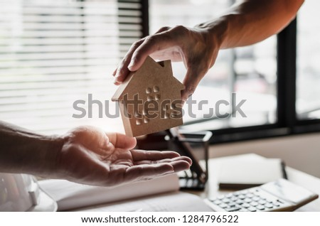 real estate broker manager giving house model to client customer after signing contract for buying house in estate agent office, investment, home loan contract, insurance, buy and sell house concept