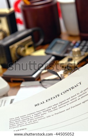 Real estate broker sale contract document on busy Realtor desk in realty agent office (fictitious document with authentic legal language)