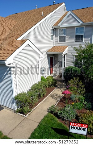 Real estate broker sold rider insert on a Realtor sign on the front lawn of a house for sale viewed from above