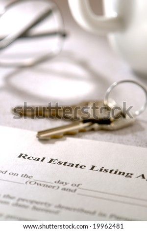 Real estate brokerage home listing contract agreement and set of house keys on a kitchen table