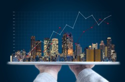 Real estate business investment and building technology. Hand holding digital tablet with buildings hologram and raising graph