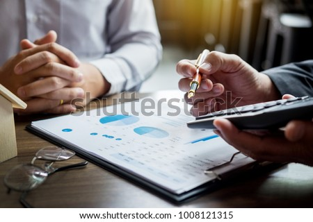 Real Estate concept, Agent holds calculator for present price for loan investment chart graph documents and calculating table payment to customer #1008121315
