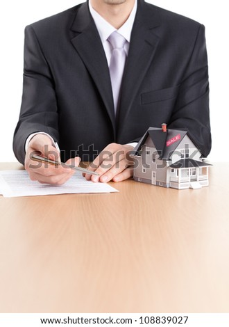 Real estate concept - business-man signs contract behind household architectural model