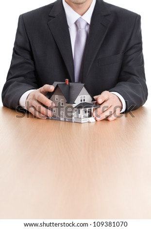 Real estate concept - businessman hands around home architectural model