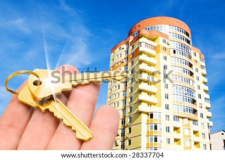 real estate concept. gold keys in fingers with building