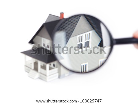 Real estate concept - hand holding magnifying glass in front of the house architectural model, isolated
