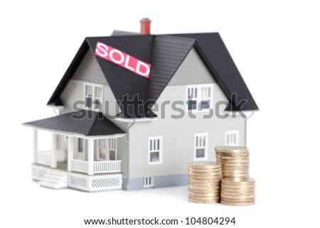 Real estate concept - stacks of coins in front of household architectural model, isolated