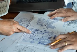 Real-estate concept, Two engineer and architect discussing blueprints data working and digital tablet on construction building project.
