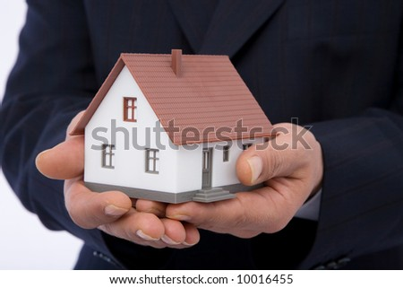 real estate concept with businessman holding mini house