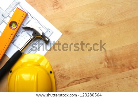 real estate concept with hard hat blueprints tools and copyspace - stock photo