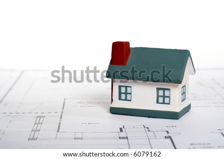 Real Estate Concept with Miniature Home atop blueprints.