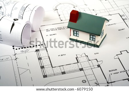 Real Estate Concept with miniature home atop home blueprints.