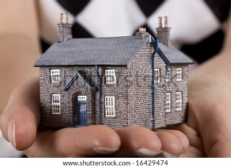 Real estate concept, woman holding model house