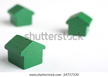 Real estate conceptual image with house tokens over a white surface