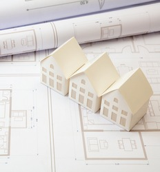 Real estate, construction blueprints concept. Residence complex architectural drawings and detached houses models on an office desk. Architect engineer work space