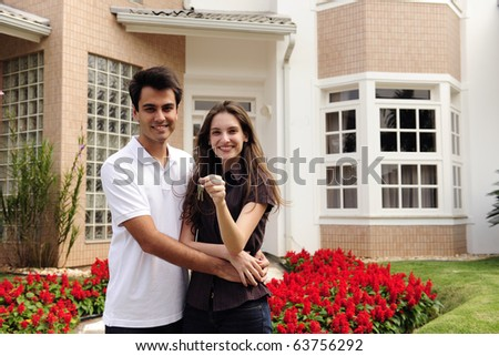 real estate: couple showing keys of their new house