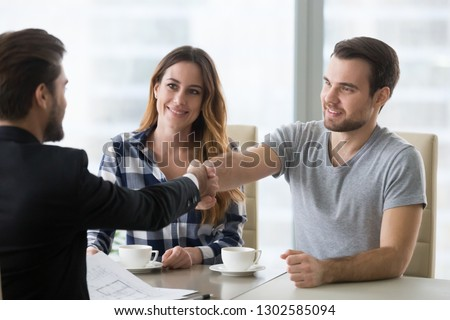 Real estate deal concept, happy couple customers handshaking realtor agent or designer at meeting, satisfied property owners and bank broker shake hands, mortgage loan investment, house purchase