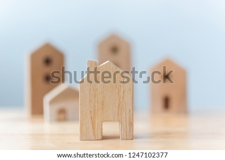 Real estate developer and managing property investment concept. Selective focus wooden houses on table