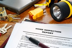 Real estate home inspection report of resale residential property condition with professional housing engineering inspector testing tools and house keys (fictitious but realistic document)