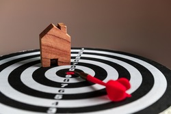Real estate investment target. Red arrow and house model on dartboard. New Year goals, new home, home ownership, mortgage investment and housing concepts. Horizontal close-up.
