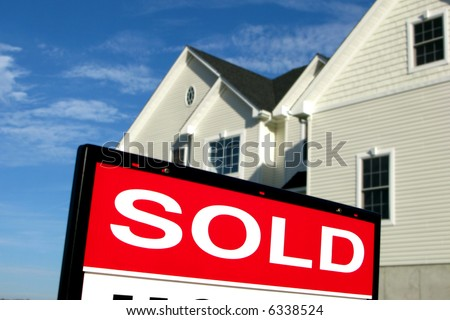 Real estate lawn sign sold rider insert in front of a house for sale by Realtor in a residential neighborhood