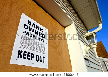 Real estate lender bank owned keep out sign notice posted on a boarded up abandoned foreclosed house in foreclosure proceedings (fictitious document with authentic legal language)