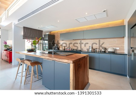 real estate Luxury interior design pool villa in kitchen area which feature island counter and built in furniture  #1391301533