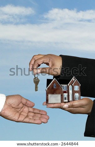 real estate market concept photo of a home sale shoeing african american hands transferring over the house and keys. Includes a clipping path.