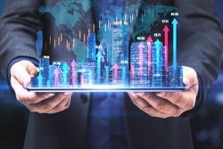 Real estate market index concept with developer and virtual financial chart growing arrows on night city buildings background on digital tablet screen