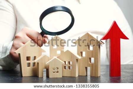 Real estate market valuation. Wooden houses and up arrow. The increased in housing prices. Rise price for utilities / rent. Increased demand for housing. Mortgage interest rates are rise. Growth