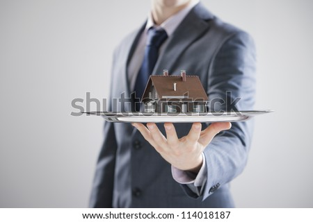 Real estate offer. Businessman holding a silver tray with an artificial model of the house