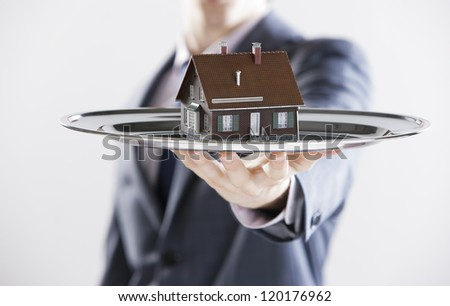 Real estate offer. Businessman holding a silver tray with an artificial model of the house - stock photo