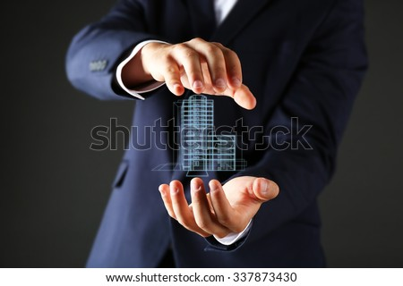 Real estate offer. Businessman holds an artificial model of the house ストックフォト ©