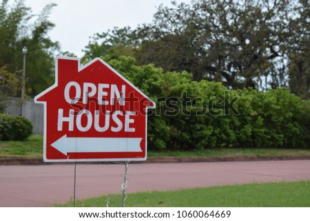 Real estate open house sign on lawn in nice suburban neighborhood.